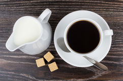 Black coffee in cup, jug milk and brown sugar. On wooden table. Top view Royalty Free Stock Photo