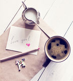 Black coffee in a cup and milk with card and envelope with wotds Royalty Free Stock Images
