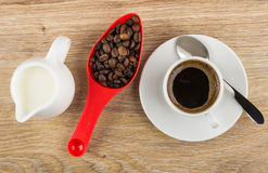 Black coffee in cup, milk, coffee beans in spoon. On wooden table. Top view Stock Images