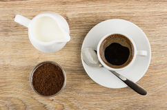 Black coffee in cup, milk, ground coffee in bowl. On wooden table. Top view Stock Photos