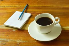 black coffee cup with note book and pencil on table Royalty Free Stock Photos