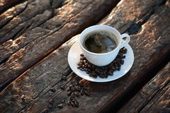 Black coffee in the cup on old wood table with coffee beans Royalty Free Stock Photography