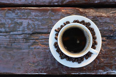 Black coffee in the cup on old wood table with coffee beans Stock Image