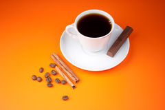 Black coffee cup on orange with piece of chocolate royalty free stock photo