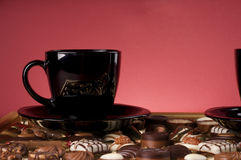 Black coffee cup over chocolate sweets. Stock Photo