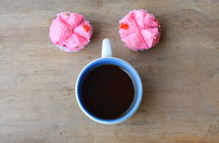 Black coffee cup and pink dessert trolley on wooden table Stock Photos