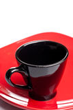 Black coffee cup on a red plate Stock Images