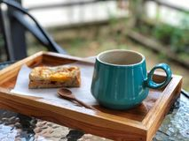 Black coffee cup and sandwich on the wooden tray. Breakfast on garden stock photo