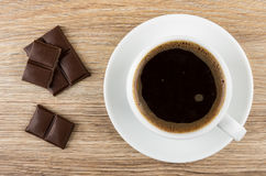 Black coffee in cup on saucer and pieces of chocolate Royalty Free Stock Photos