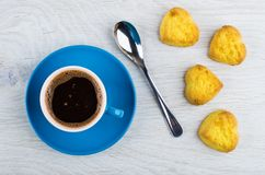 Black coffee in cup on saucer, spoon, cookies. Black coffee in blue cup on saucer, spoon, cookies in form heart on wooden table. Top view Stock Image