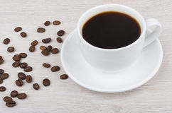 Black coffee in cup and scattered coffee beans on table Stock Photos