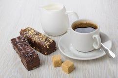 Black coffee, spoon, chocolate wafer, jug of milk and sugar. Black coffee in cup, spoon, chocolate wafer, jug of milk and sugar on wooden table stock images
