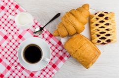 Coffee in cup, spoon, milk on napkin, different pastry. Black coffee in cup, spoon, jug of milk on napkin, different pastry in plate on wooden table. Top view Royalty Free Stock Photography