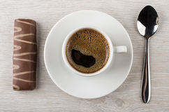 Black coffee in cup, striped chocolate candy and spoon Stock Photos
