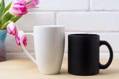 Black coffee cup and white cappuccino mug mockup with magenta tu Stock Image