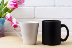 Black coffee cup and white latte mug mockup with magenta tulip Royalty Free Stock Photos