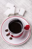 Black coffee cup with sugar lumps. Black coffee cup with white sugar lumps view from above Stock Photo