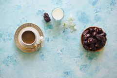 Black coffee, dates and a glass of milk on a turquoise background. Ramadan food. Black coffee, dates and a glass of milk on a turquoise background. Ramadan food royalty free stock image