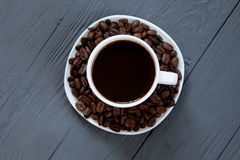 Black coffee drink in a cup and coffee beans on wooden surface Royalty Free Stock Image