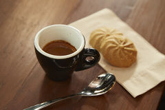 Black coffee is eaten with cookie Stock Images