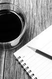 Black coffee and an empty notebook with pencil on wooden table. Royalty Free Stock Image