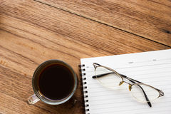Black coffee, eye glasses and notebook. Stock Images