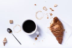 Black coffee with fresh croissant for breakfast on white table. Stock Images