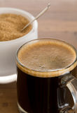 Black coffee and froth in glass mug with sugar stock photos