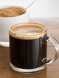 Black coffee and froth in glass mug with sugar royalty free stock images