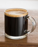 Black coffee and froth in glass mug wood table Royalty Free Stock Photography