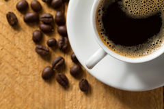 Black coffee with froth on wooden table Royalty Free Stock Image