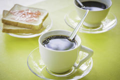 Black coffee in a glass with bread. Black coffee in a glass with bread on the table Royalty Free Stock Photo