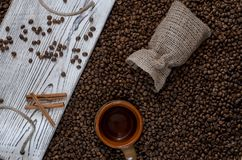 Black coffee grain scattered on the table from a plain bag royalty free stock images