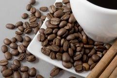 Black coffee, grains and cinnamon Royalty Free Stock Photo