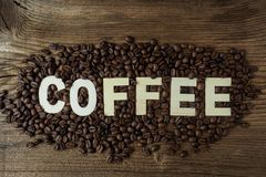 Black coffee grains lie on a brown wooden table. The word `coffee Stock Image