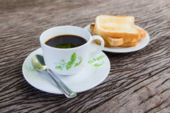 Black coffee with grilled bread. On the old wood Stock Photo