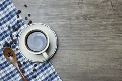 Black coffee intense in cup and wooden Spoon Scoop Roasted Coffee Beans stock image