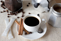 Black coffee with italian coffee pot, beans and cinnamon Royalty Free Stock Photography