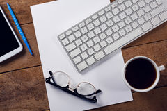 Black coffee, keyboard, spectacles and paper on wooden table. Close-up of black coffee, keyboard, spectacles and paper on wooden table Royalty Free Stock Photography