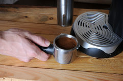 Black coffee machine and male hand on a wooden background Stock Image