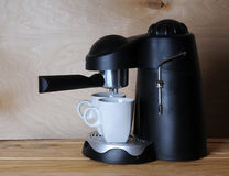 Black coffee machine with two white cups on a wooden background Royalty Free Stock Photo