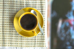 Black coffee on mat and blurry pool having carps Royalty Free Stock Photo