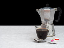 Black coffee and medication for one person, grungey look. Stock Photography