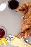 Black coffee, milk, croissants, jam, fruit and toast on a light Royalty Free Stock Photos