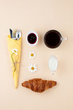 Black coffee, milk, fresh croissant and jam on a light yellow ba Stock Image