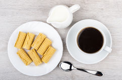 Black coffee, milk jug and rolls wafers in plate. On wooden table. Top view Stock Photo