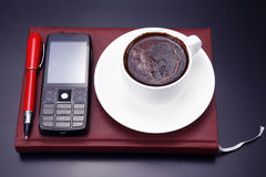 Black coffee, mobile and pen on the table from a business person Stock Photos