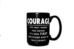 Black coffee mug with an inspirational quote. This image consists of a black coffee mug with an inspirational quote which says life may knock you down, it`s how stock photos