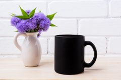 Black coffee mug mockup with blue Ageratum in pitcher Royalty Free Stock Images