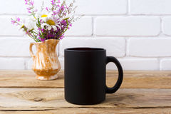 Black coffee mug mockup with chamomile and purple flowers in gol Stock Photography